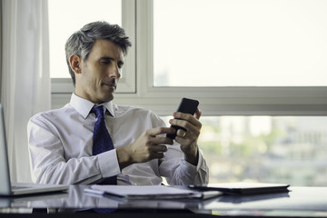 Man using smart phone in office