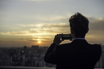 Man taking photograph of sunset