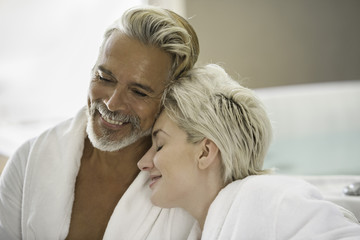 Couple in bathrobes smiling