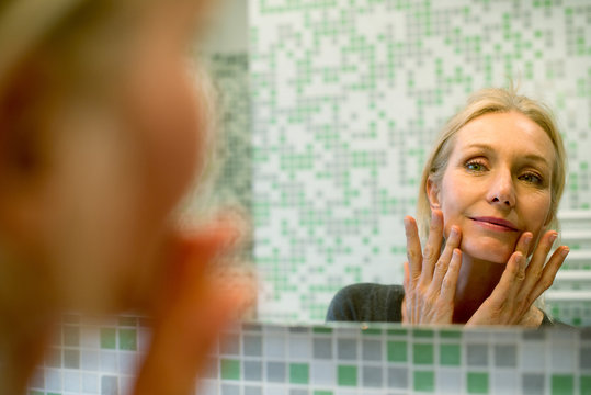Mature woman scrutinizing her face in bathroom mirror
