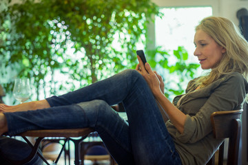 Mature woman relaxing with smartphone at home