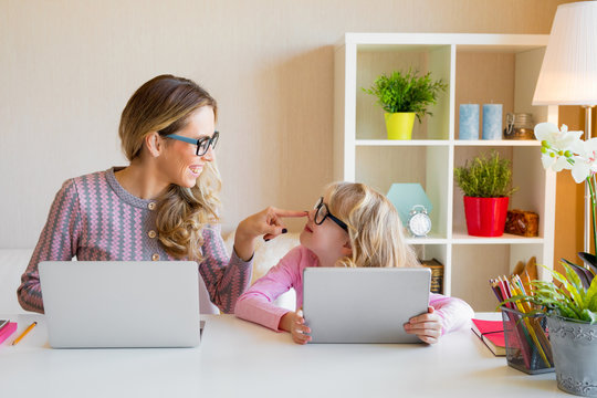 Mother and daughter sitting at table and using computers together