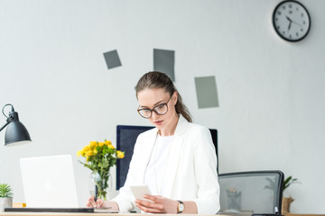 portrait of businesswoman using smartphone while doing paperwork at workplace in office