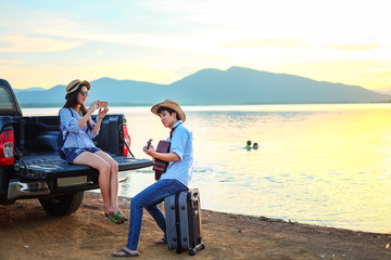 couple traveler playing guitar and watching sunset near the lake background  the mountain.Asia tourist enjoying for sunset during holiday