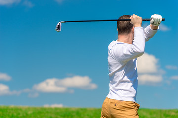 male professional golfer while hitting the ball from the back