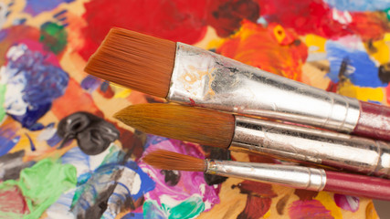 Artist. Creativity. Art. Set of brushes on wooden palette stained with paints