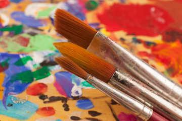 Painting. Set of brushes on the palette stained with paints