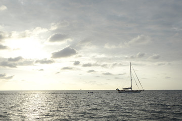 cloudy sky and sunset with boat sailing through on the ocean in the nice day