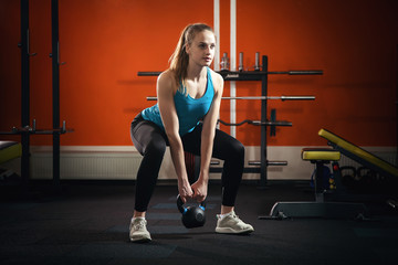 Slender athletic girl crouches with dumbbells in the gym.