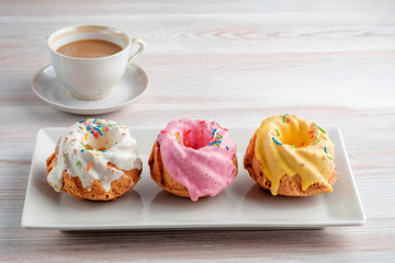 Three multi-colored cupcakes on a rectangular plate and a cup of espresso on a light table texture. Copy space your text.