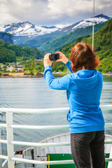 Tourist woman on liner taking photo, Norway