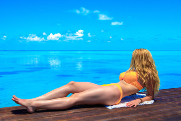 Blond woman with bikini on the wooden pier at the sea