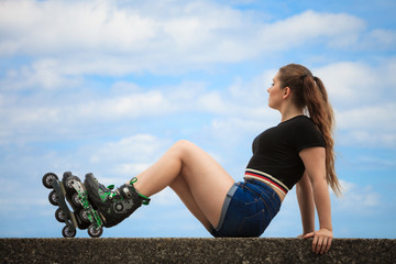 Happy young woman wearing roller skates