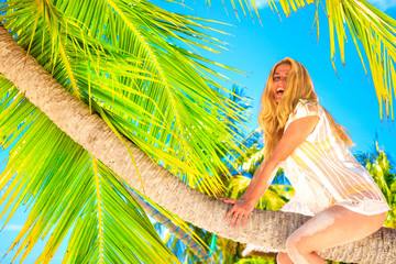 Blond woman sits on the palm tree on the sandy beach by the sea on Maldives