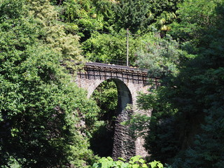 View of stony funicular railway bridge of tourist train in european Locarno city, green plants and trees in Switzerland