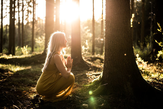 Junge Frau betet im Wald zum Sonnenuntergang