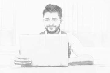 Smiling bearded businessman working at a laptop