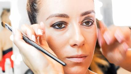 Closeup image of makeup artist hands touching models face