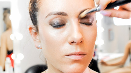 Closeup image of makeup artist painting model's eyelids with brush