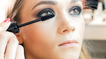 Closeup image of young blonde woman painting eyes with mascara