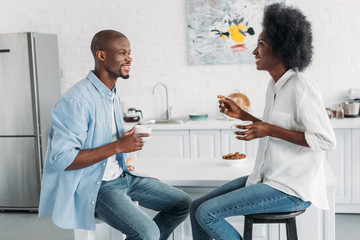 side view of african american couple with cups of coffee in morning together in kitchen at home