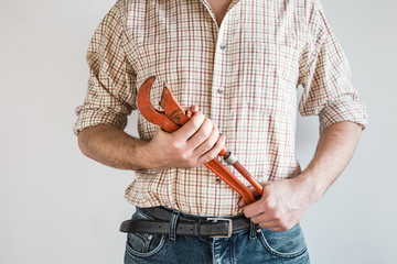 Adjustable wrench in adult man's hands. Confident plumber in simple checkered shirt and jeans. Ready for work. Gray background. Plumbing service concept. Front view.