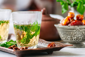 Traditional moroccan mint tea with dates on a vintage tray. White stone background.