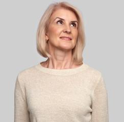 Beautiful senior woman looking up
