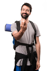Handsome backpacker doing coming gesture on white background