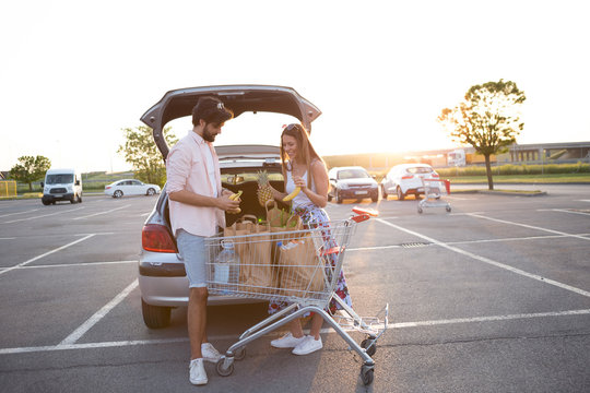 Young happy couple in front of a supermarket in the parking lot.