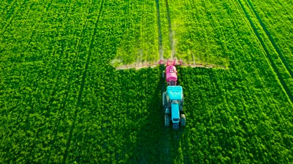 Wall Mural - Aerial view of farming tractor plowing and spraying on green spring field
