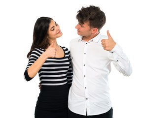 Young couple giving a thumbs up gesture and smiling on isolated white background