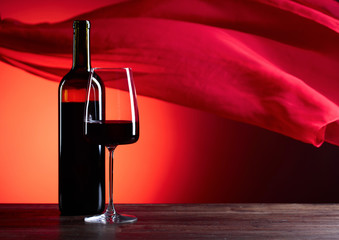 Glasses and bottle of rede wine on a red background. Red sheer fabric flutters in the wind.