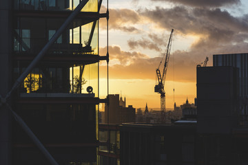 UK, London, buildings and crane silhouette at sunset with Big Ben and Westminster in far background