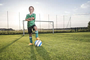 Portrait of confident young football player with ball on football ground