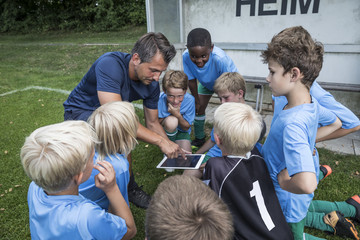 Coach with tablet and young football players on football ground