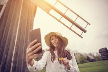 A beautiful young woman is using an application in her smart phone device, in spring time, in front of a windmill.