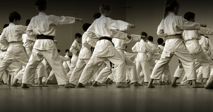 Children's training on karate-do. Banner with space for text. For web pages or advertising printing. Photo without faces, from the back.