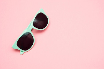Green pastel sunglasses isolated on punchy pink, top view. Copy space. Summer concept.