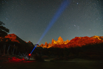 View of Mount Fitz Roy and a man with a spotlight in the National Park Los Glaciares National Park at night. Autumn in Patagonia, the Argentine side