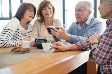 Group of senior friends looking at pictures on smartphone