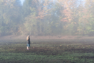 A girl with blonde hair standing in field on a foggy morning, with autumn leaves and forest in background. The woman is wearing a denim skirt and a jacket.