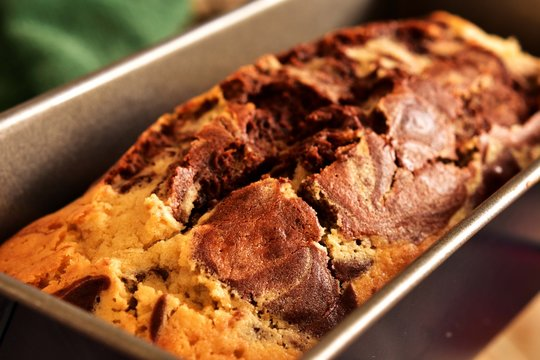 Close-up of freshly baked marbled pound cake in a loaf tin.