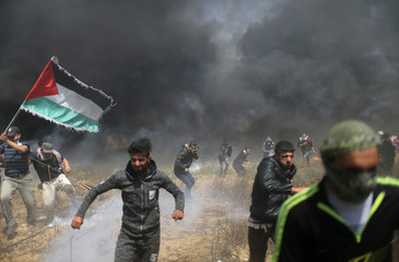 Palestinian demonstrators run for cover during clashes with Israeli troops at a protest demanding the right to return to their homeland, at the Israel-Gaza border in the southern Gaza Strip