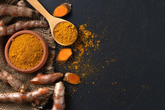 turmeric powder in spoon with turmeric root