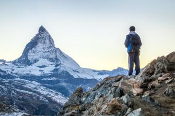 Fotobehang Alpinisme Junger Mann beim Bergsteigen in den Schweizer Alpen mit Matterhorn im Hintergrund