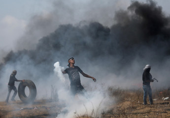 Demonstrator hurls back a tear gas canister fired by Israeli troops during clashes at a protest where Palestinians demand the right to return to their homeland, at the Israel-Gaza border in the southern Gaza Strip