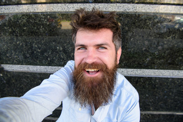 Vlogging concept. Hipster, tourist with tousled hair and long beard looking at camera, taking selfie photo. Man, tourist with beard and mustache on cheerful, smiling face, black marble background.