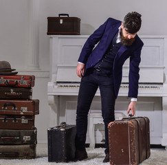 Baggage delivery concept. Man, traveller with beard and mustache with luggage, luxury white interior background. Macho elegant on strict face stands near pile of vintage suitcase, holds suitcase.