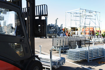 Modern electric forklift carries special metal structures for the construction and erection works